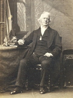 Photograph of the Revd Henry Venn Elliott seated at his desk.